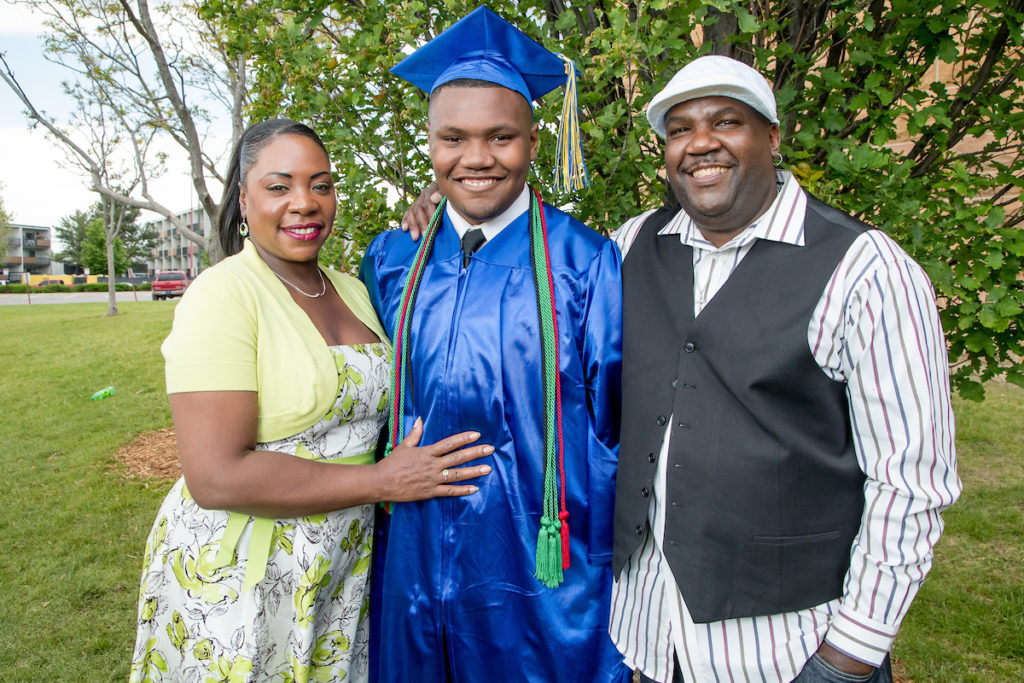 male high school graduate with his parents