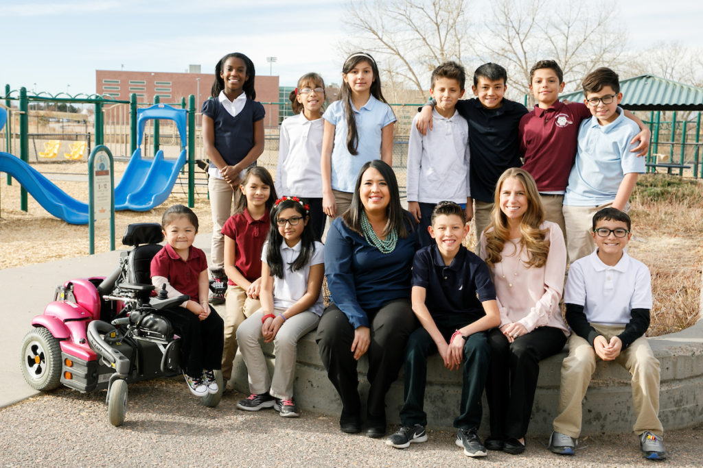 Principal, assistant principal and a large group of elementary students on a playground