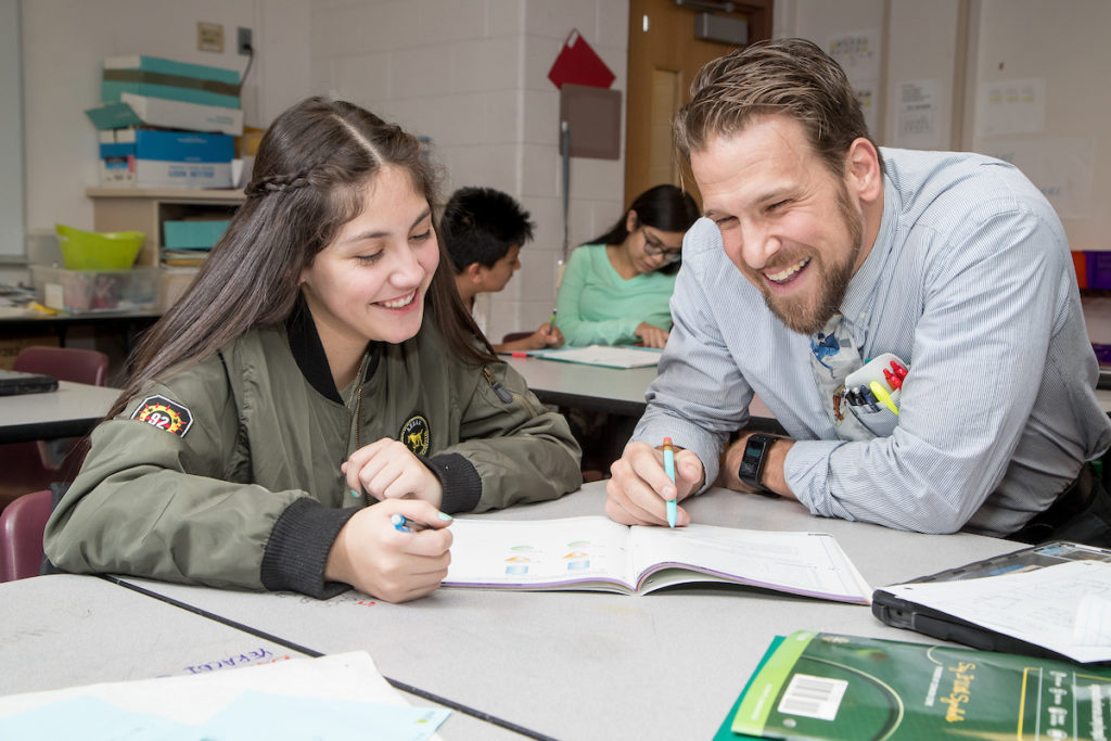Male teacher and female high school student sitting at a table looking at a workbook