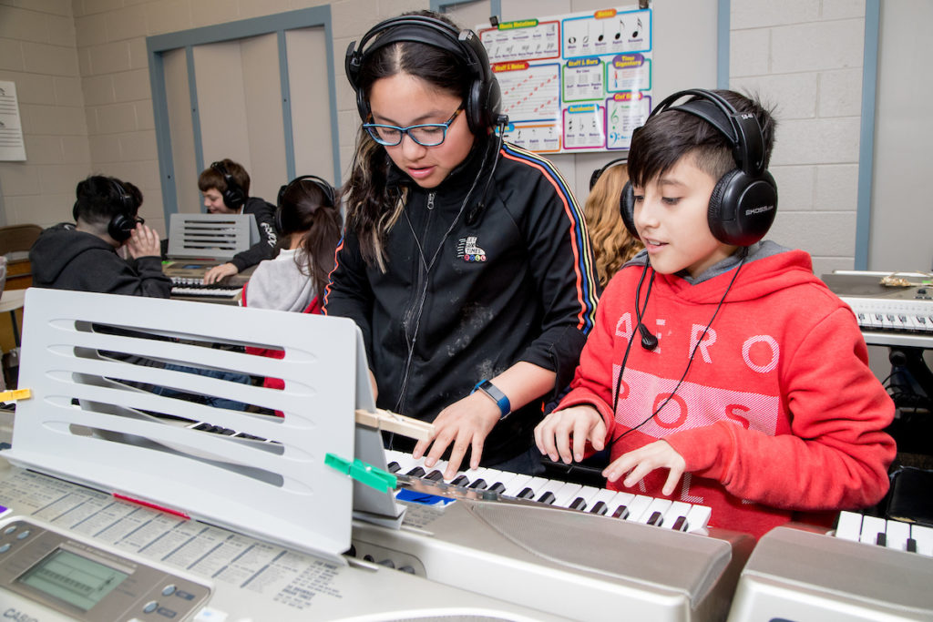 Two middle school students playing a piano with headphones on