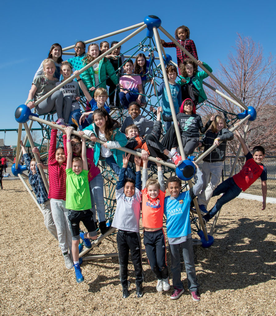 Large group of elementary students playing on a large set of monkey bars