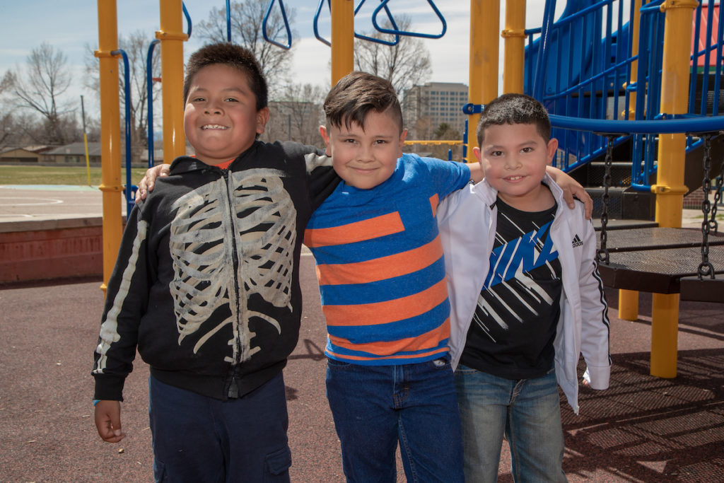 Three elementary school boys standing arm-in-arm in front of a playground