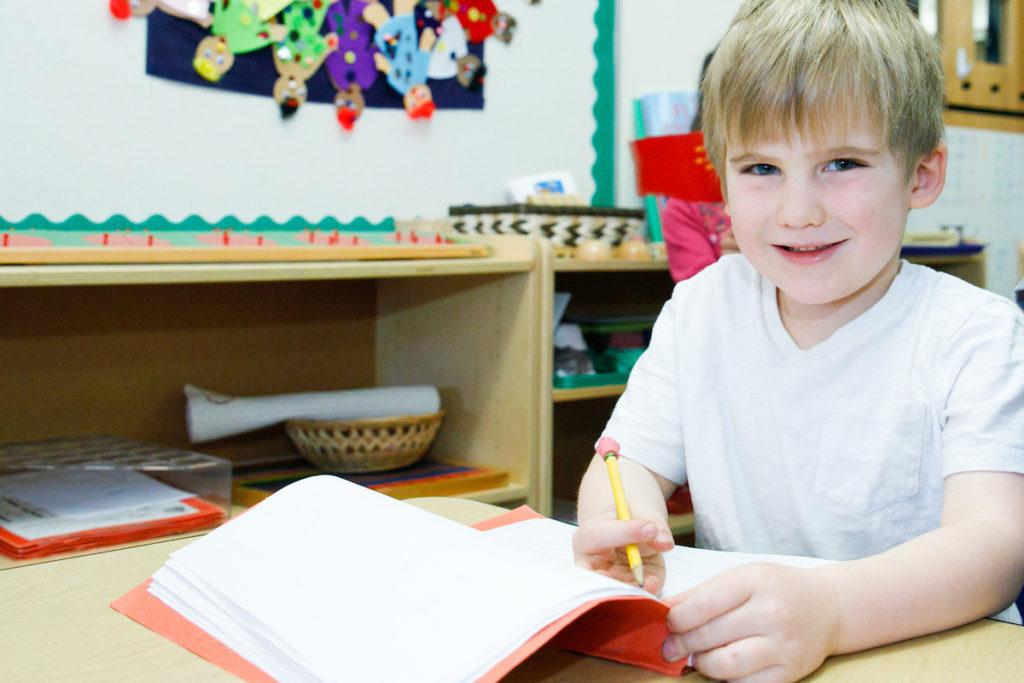 an elementary school boy using his pencil in his orange folder