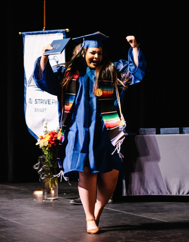 Female high school graduate celebrating with her arms up in the air on stage after she receives her diploma